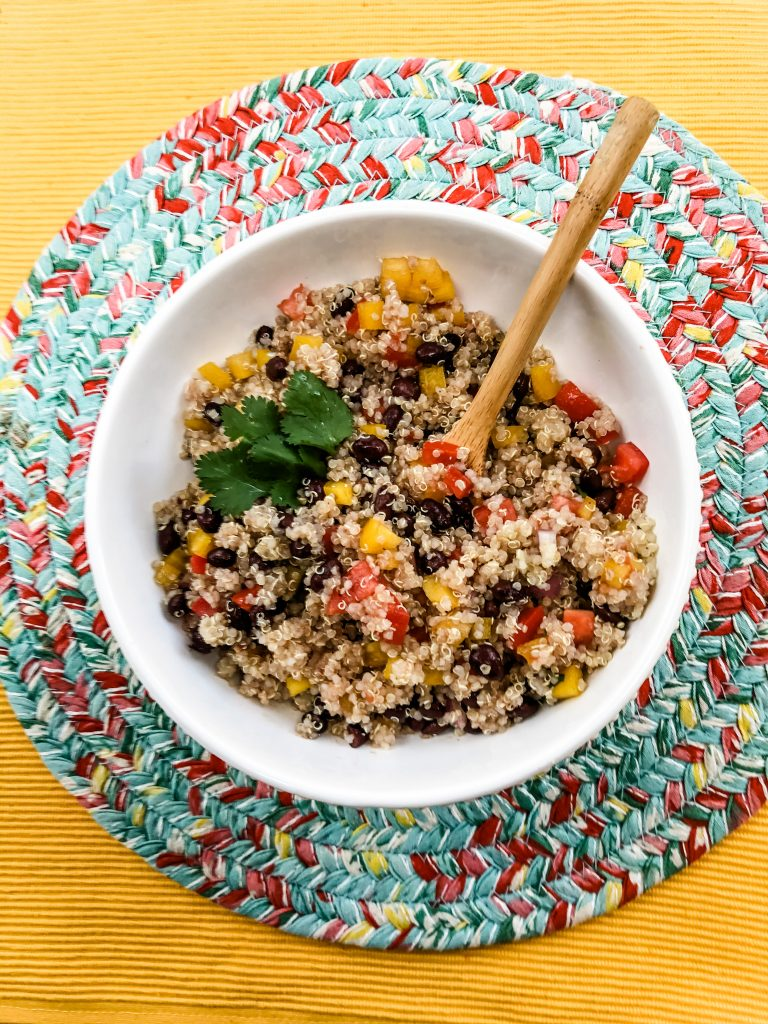 finished mexican quinoa with cilantro and wooden spoon on mat