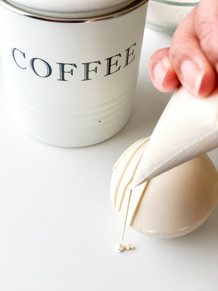 decorating coffee bombs with chocolate drizzle and coffee canister in background