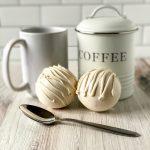 white chocolate coffee bombs with spoon, mug, and coffee canister