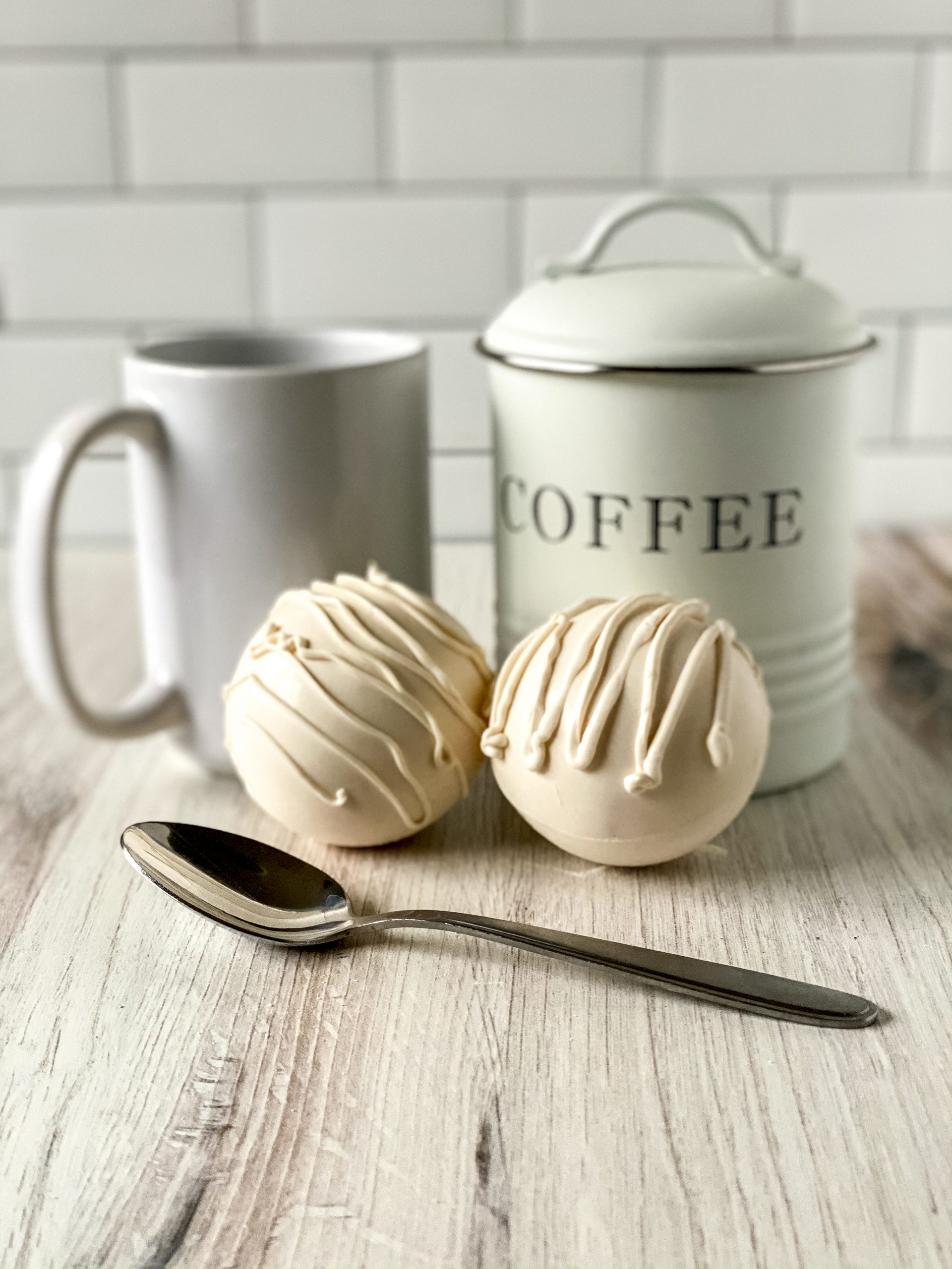 white chocolate coffee bombs with spoon, mug, and coffee canister