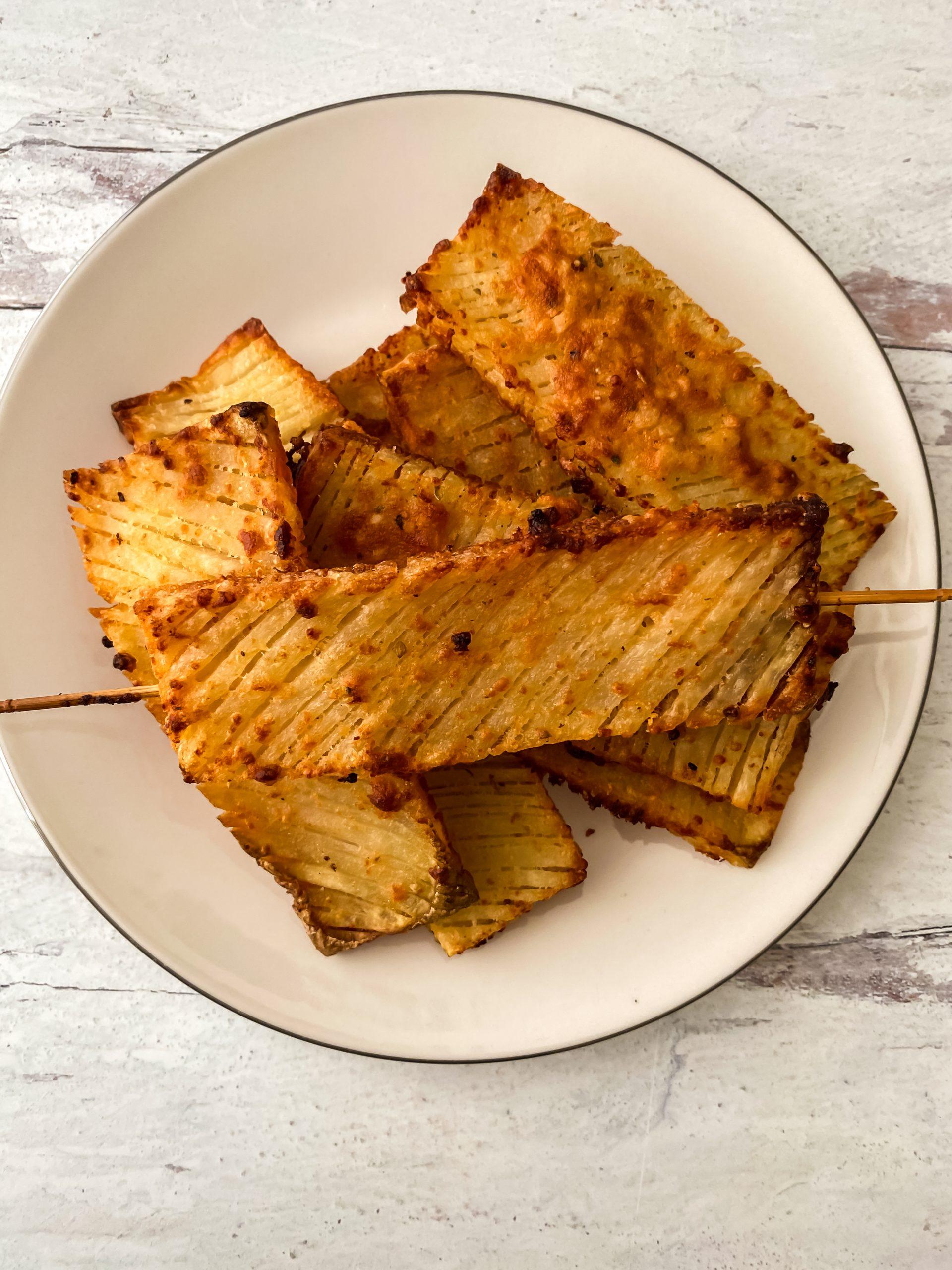 garlic parmesan hasselback waffle potatoes served on white plate