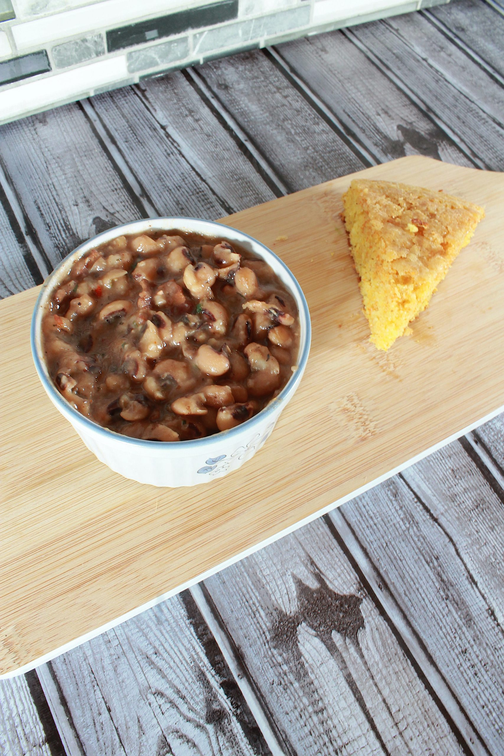 vertical image of instant pot black eyed peas in a bowl with wedge of cornbread