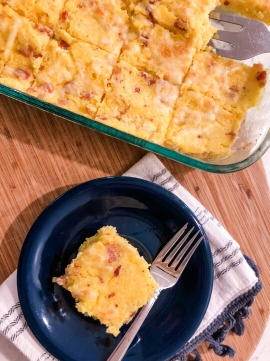 casserole dish of cheddar bacon polenta squares with one square plated