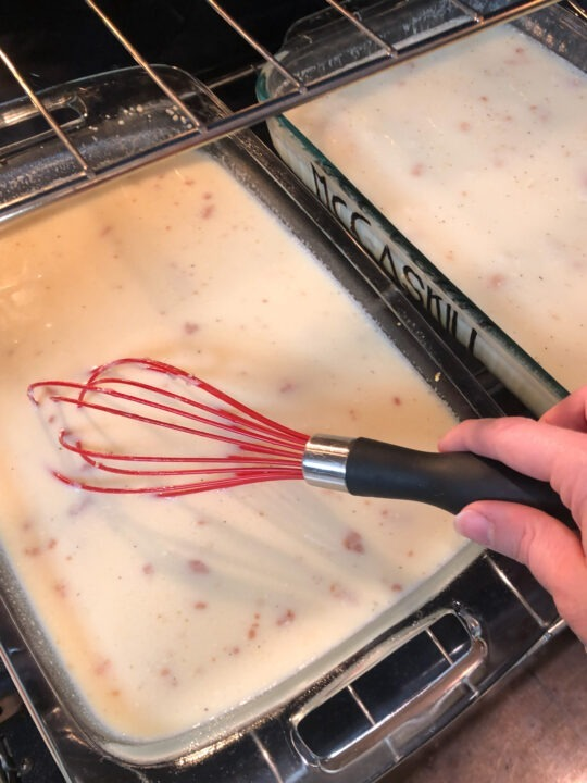 whisking the boiling water in the pan of polenta in oven